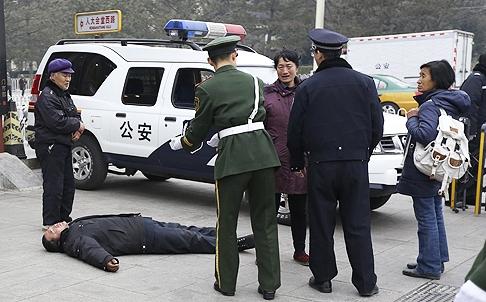 Policjanci namawiają do wstania człowieka, który przyjechał do Pekinu złożyć petycję i próbuje ściągnąć na siebie uwagę gapiów i dziennikarzy.