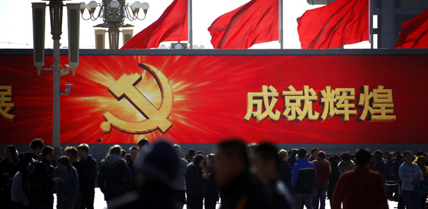People walk in front of a large screen displaying propaganda slogans on Beijing's Tiananmen Square