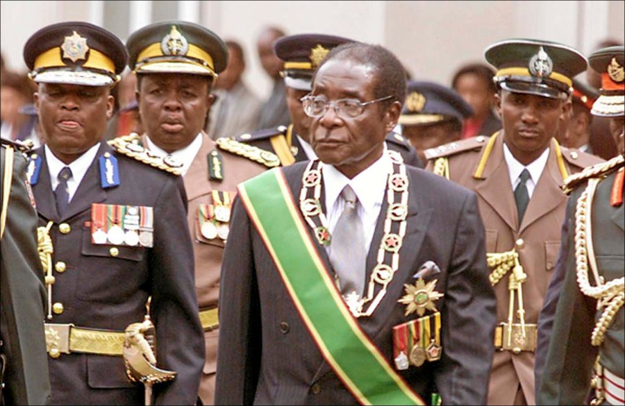 President Robert Mugabe, center, inspects a guard of honor at the opening of Parliament in Harare, Zimbabwe Tuesday, July 22, 2003. Opposition lawmakers decided not to walk out of the ceremony breaking their boycott of official events addressed by Mugabe. (AP Photo)