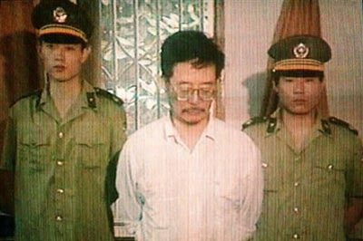 """A 1995 photo shows US human rights activist Harry Wu (C), standing between two Chinese policeman taken from a video offered for sale to foreign news agencies. After languishing 19 years in China's forced labour camps, a Chinese dissident has set up a museum in Washington to highlight the """"horrors and atrocities"""" in these secret detention facilities."""
