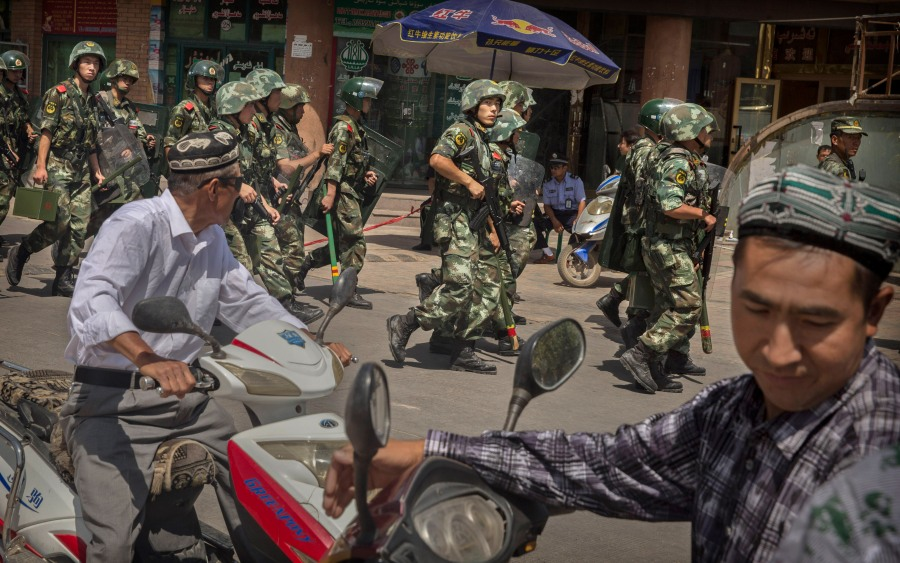 KASHGAR, CHINA - JULY 31: Chinese soldiers march past near the Id Kah Mosque, China's largest, on July 31, 2014 in Kashgar, China. China has increased security in many parts of the restive Xinjiang province following some of the worst violence in months in the Uyghur dominated area. (Photo by Getty Images)